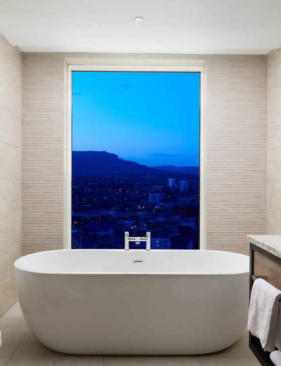 A cream bathroom with a bathtub that looks out over the city through a long glass window