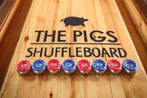 A wooden table with the words 'The Pigs Shuffleboard' written on and a drawing of a pig
