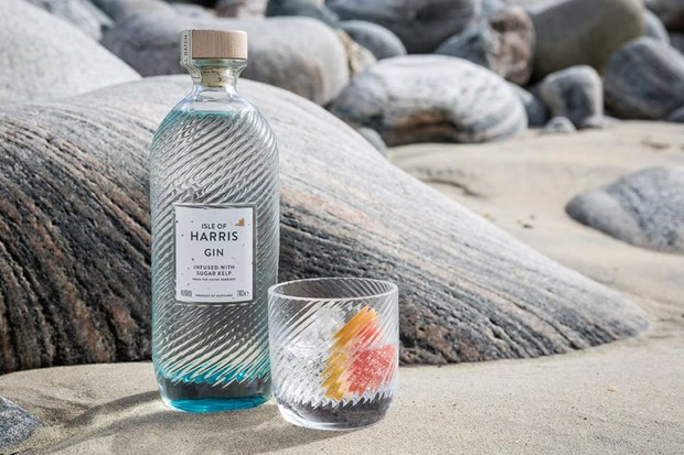 Isle of Harris Gin with a glass of gin on a beach