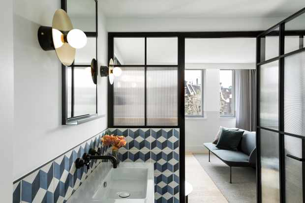 A large tiled bathroom with glass partition looking through to a living area