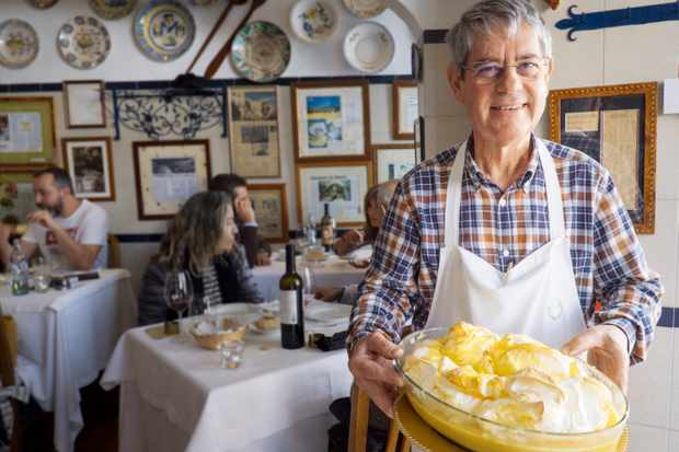 A man wearing a white apron is stood holding a bowl of yellow pudding. Behind him there are people sat at tables eating and drinking wine