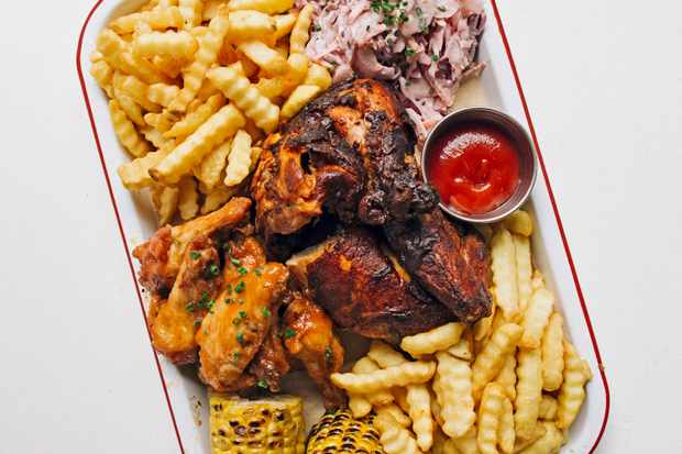 A white tray topped with fried chicken, crinkle fries and a pot of red tomato sauce