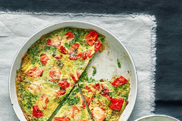 A frying pan filled with a yellow frittata with red peppers and green peas