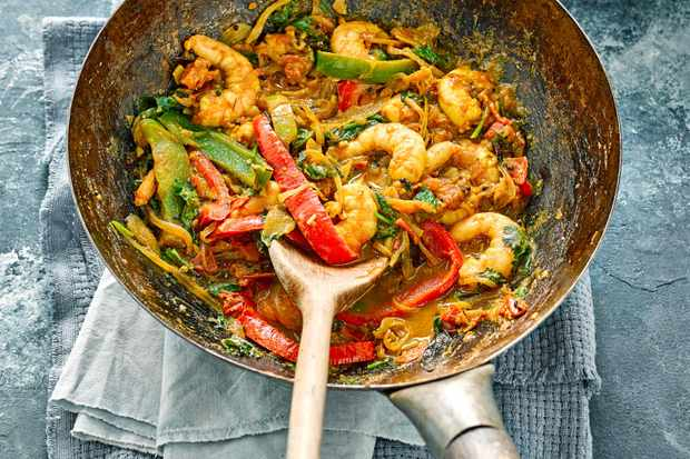 A silver wok is filled with prawns, chopped peppers and green vegetables