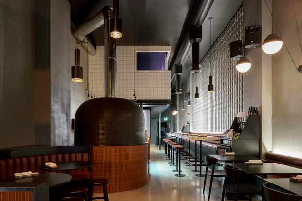 A dark room with a pizza oven and bar seats