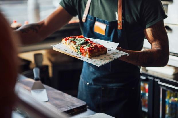 شخصی که تخته ای در دست دارد و روی آن یک تکه پیتزا قرار دارد