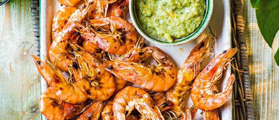 A silver tray topped with juicy pink prawns with a green sauce on the side