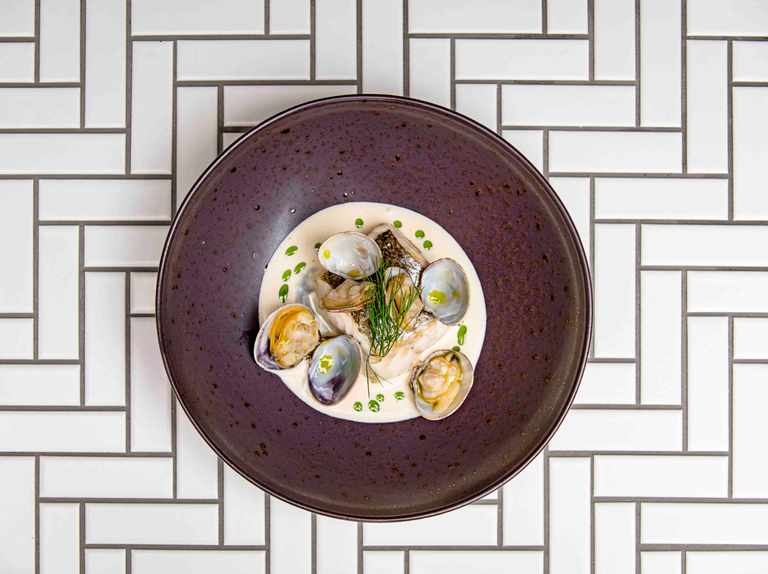 Roasted hake with clams, cider sauce and dill oil