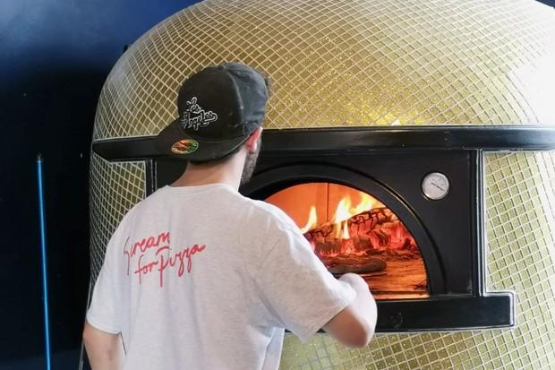 مردی که یک پیراهن سفید پوشیده و یک پیتزا در اجاق گاز قرار می دهد