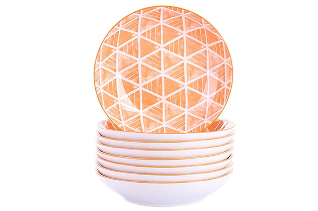 A set of orange bowls piled on top of each other with a white geometric design on