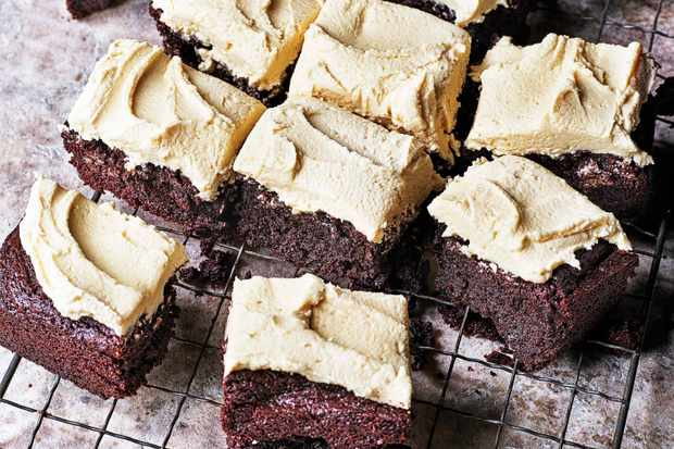 Squares of brown chocolate brownies topped with cream buttercream sat on a metal cooling tray