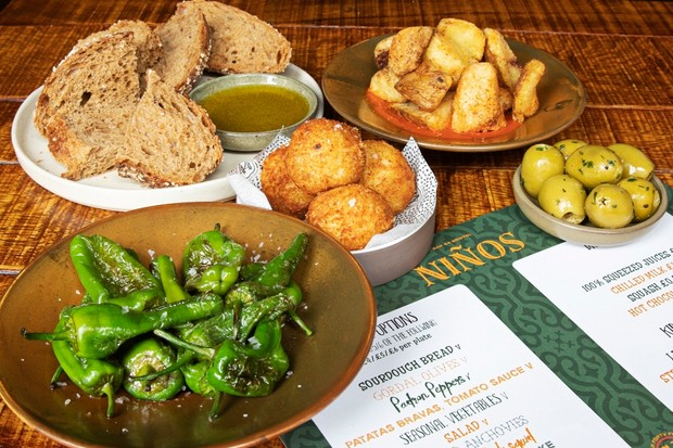 A wooden table laid with small plates of green peppers, croquettes and green olives