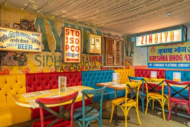 A colourful room filled with yellow, blue and red wooden tables