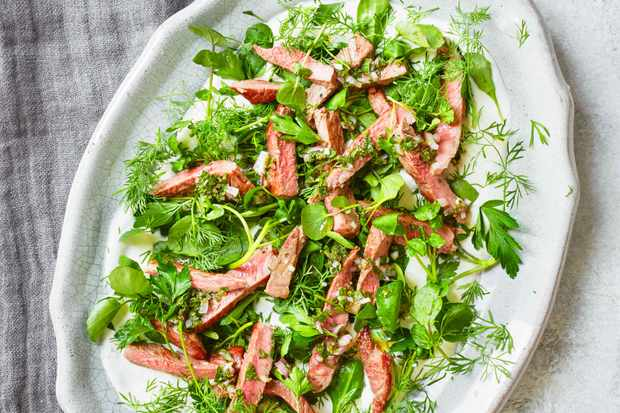 A white platter with green leaves and slices of pink lamb