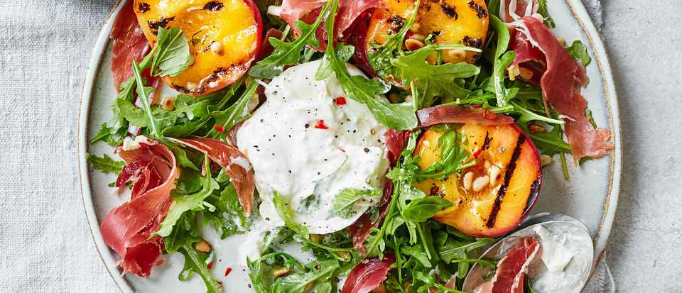 A grey plate topped with green leaves, orange peaches and a ball of white cheese