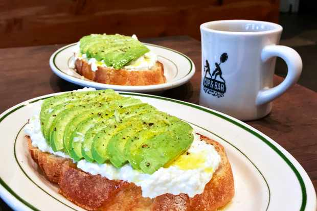 Two slices of sourdough topped with white ricotta and slices of green avocado