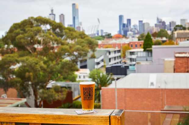 Une pinte de bière perchée sur un rebord avec les toits de la ville de Melbourne en arrière-plan