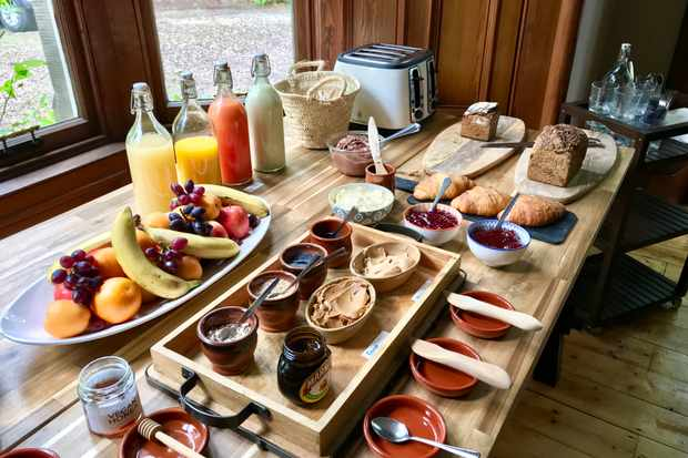A large wooden table spread with jams, nut butters, croissants and a fruit bowl
