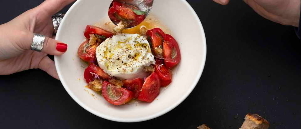 A white bowl filled with creamy burrata and small red tomatoes