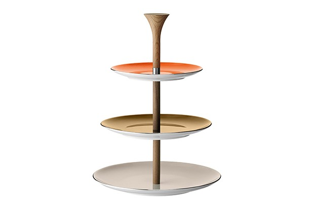 A three-tier cake stand with wooden stand