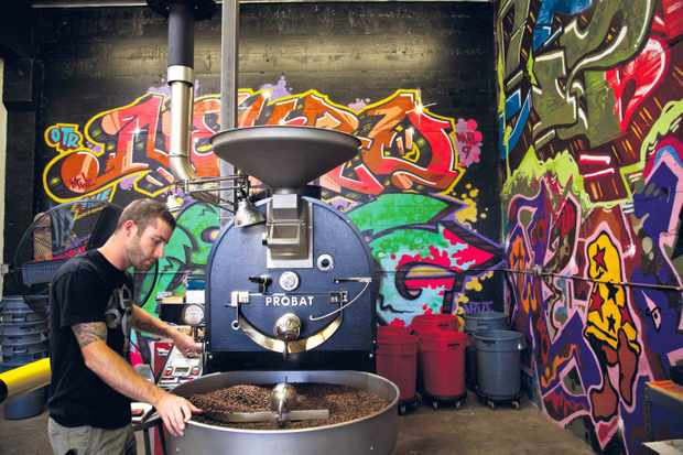 A industrial factory with a colourful mural and a man working with coffee beans