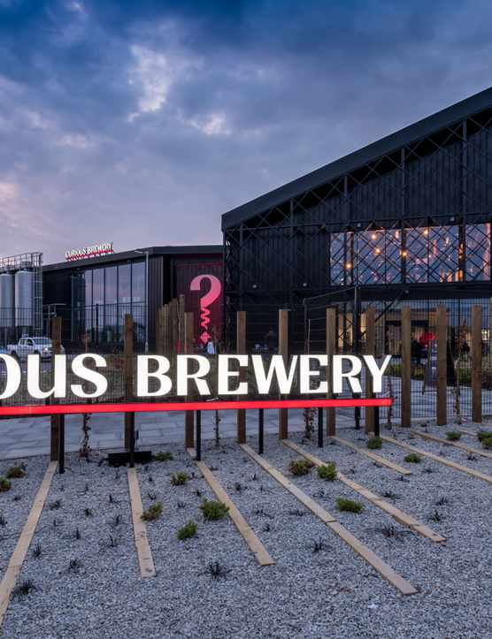 A modern building with a bright sign outside that reads Curious Brewery