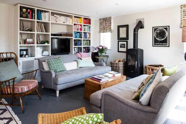 A living room with grey sofas, log burning fire and bookshelves filled with books