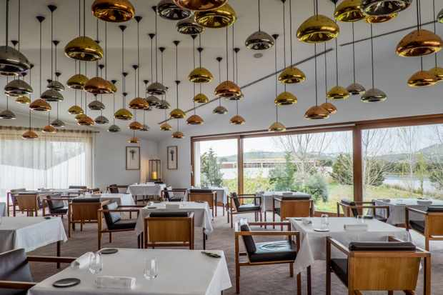 A large restaurant with long glass windows, tables laid with white cloths and gold lights hanging from the ceiling