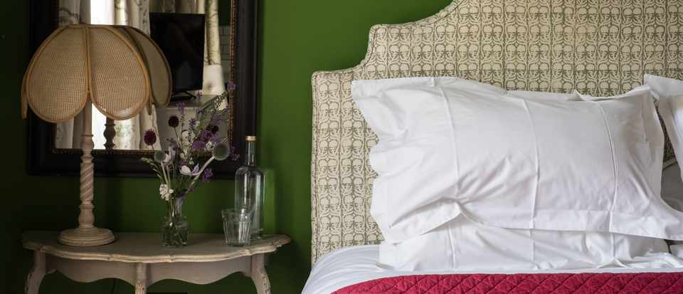 A bedroom with pea green walls, a cream fabric head board and a side table with flowers on