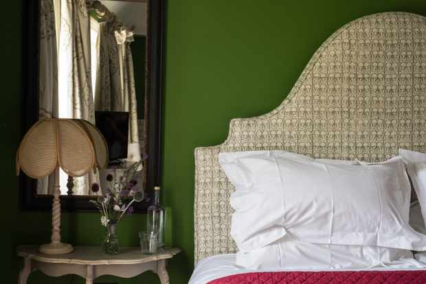 A bedroom with pea green walls, a wicker head board and a side table with flowers on