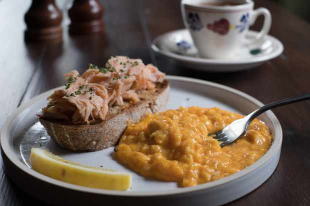 A white plate has a chunk of sourdough on top with salmon flakes, with creamy yellow scrambled eggs to the side