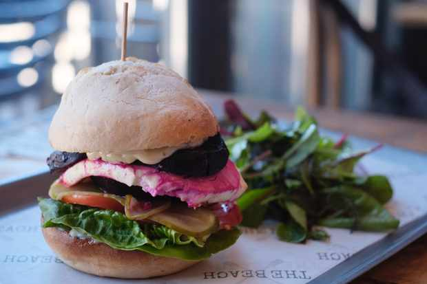 A towering vegetarian burger with a salad on the side