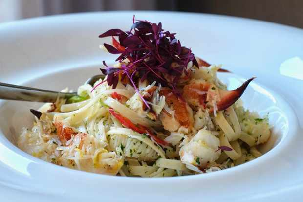 A white bowl filled with strands of linguine with crab on top