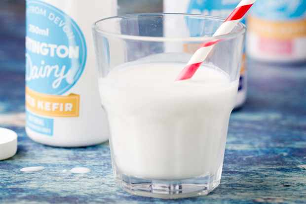 A glass of white kefir with a white bottle in the background