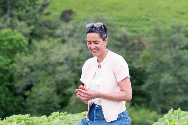 A woman sat in a field wearing a white shirt holding a strawberry