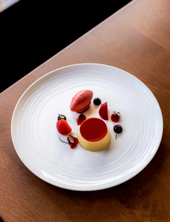 A white plate topped with a quenelle of strawberry sorbet and and a strawberry mousse