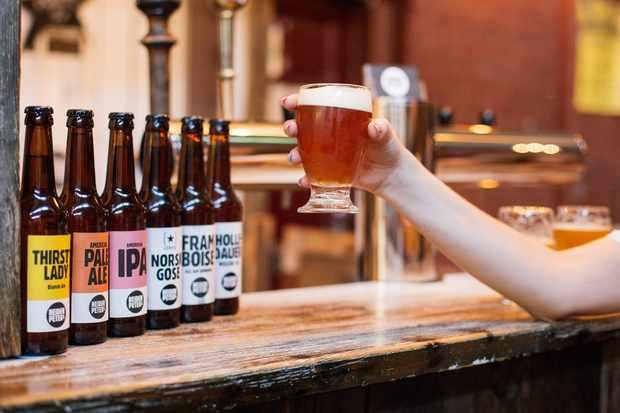 Bouteilles de bière alignées sur un bar avec une main tenant un verre