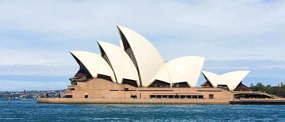 Sydney opera house against a bright blue sky