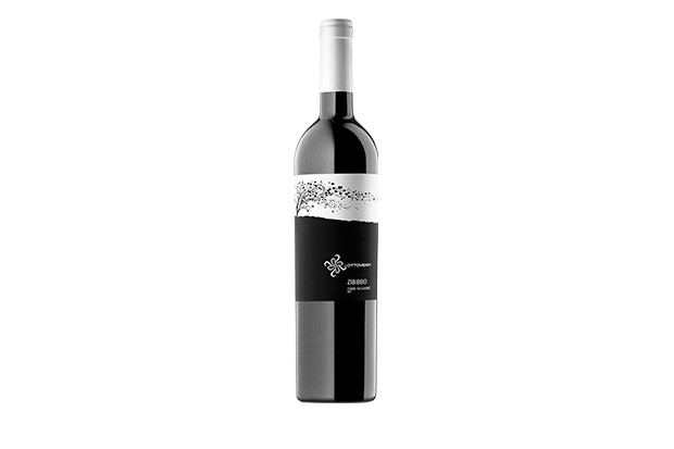 A bottle of red wine with a silver logo