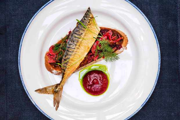 A white plate topped with a fillet of mackerel, a dollop of purple ketchup and a piece of toast topped with pink pickles