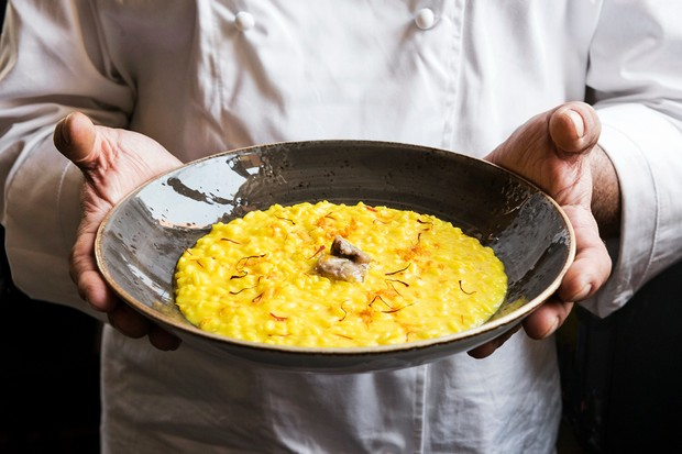 A man holding a black bowl filled with yellow risotto