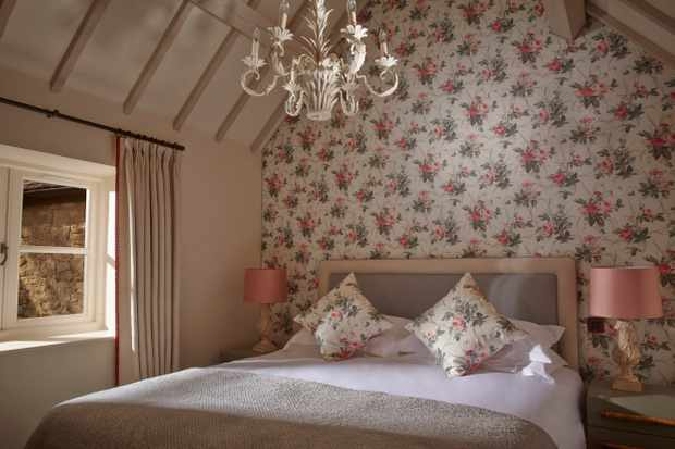 A double bedroom with beamed ceiling, pink floral wallpaper and a chandelier
