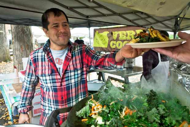 A man wearing a checked shirt passing a plate of food over to a customer at a farmers' market