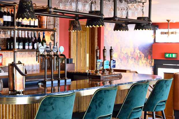 A central bar with blue velvet stools