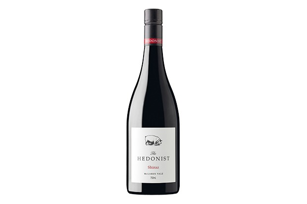 A wide bottle of red wine with a simple white label