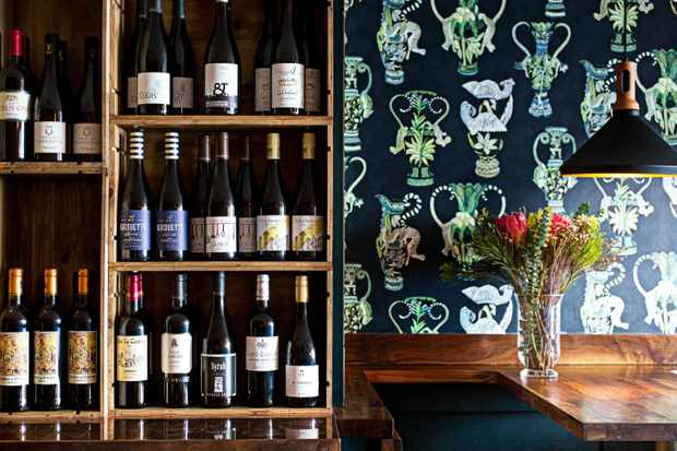 A wall lined with bottles of wine and dark blue wallpaper