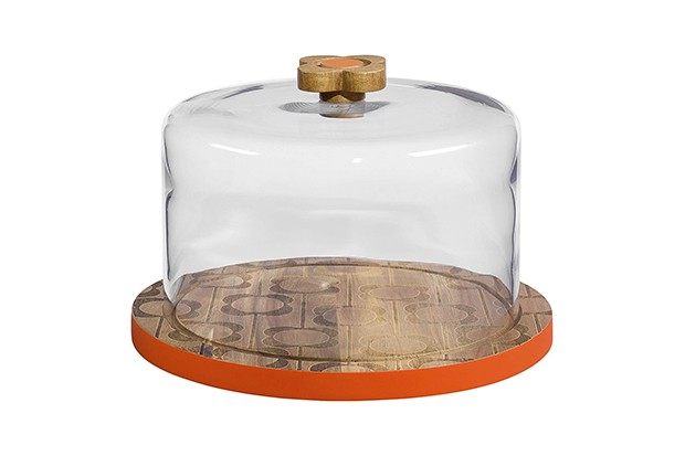 A wooden cake plate topped with a glass dome