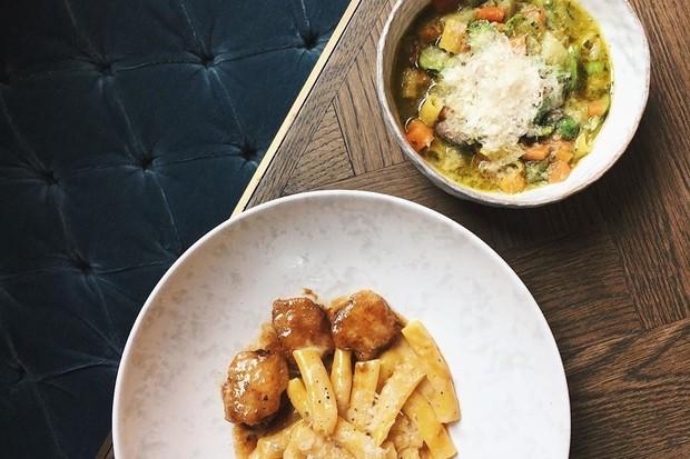 A bowl of cacio e pepe pasta with chicken wings