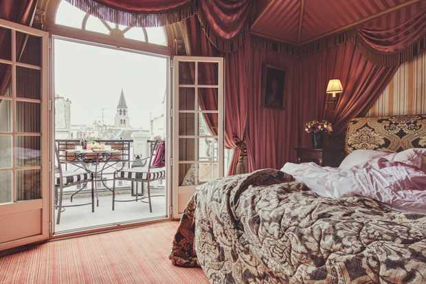 A large double bedroom with doors opening out onto a balcony with views of Paris