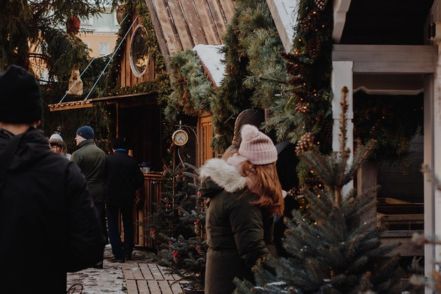 A Christmas market with wooden chalets and people stood around in coats and hats